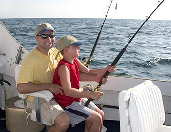 Dad and son fishing on a charter together