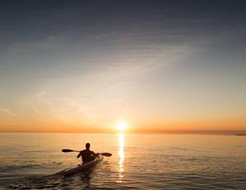 Kayaking on the water at sunset