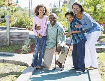 Family playing a game of mini golf