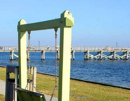 The pier and people sitting on benches at Southport in North Carolina