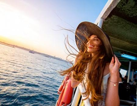 Girl holding onto her big sunhat on the ferry