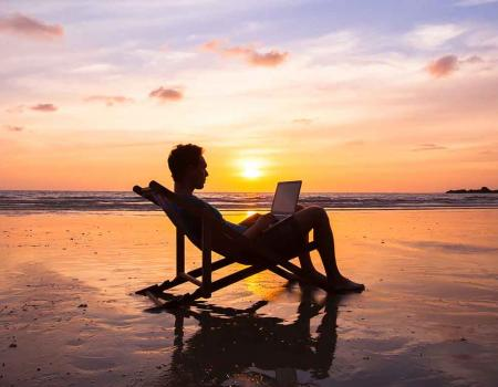Man sitting on the beach with his computer
