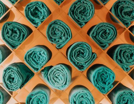 Green linen beach towels rolled up in a modern orange holder
