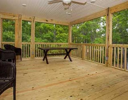 The covered porch of an Oak Island vacation rental by Rudd