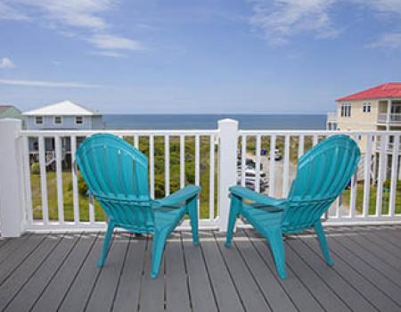 Two beach chairs on a balcony of a vacation rental
