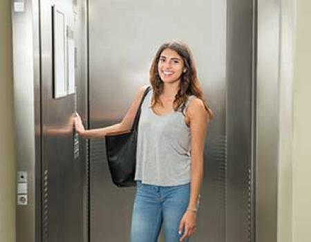 Girl standing in front of an elevator in her vacation rental home