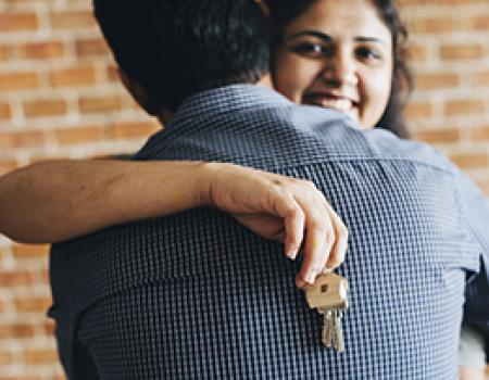 Happy wife hugging her husband after buying a new home