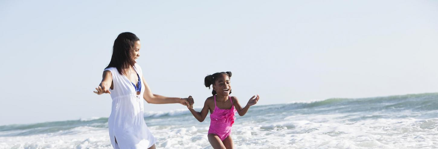 Little girl and mom playing in the ocean