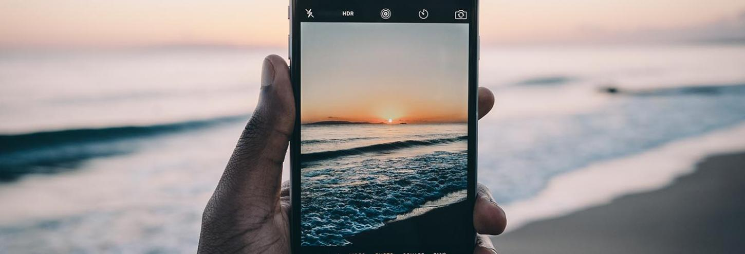 The sun setting on the beach viewed through a phone