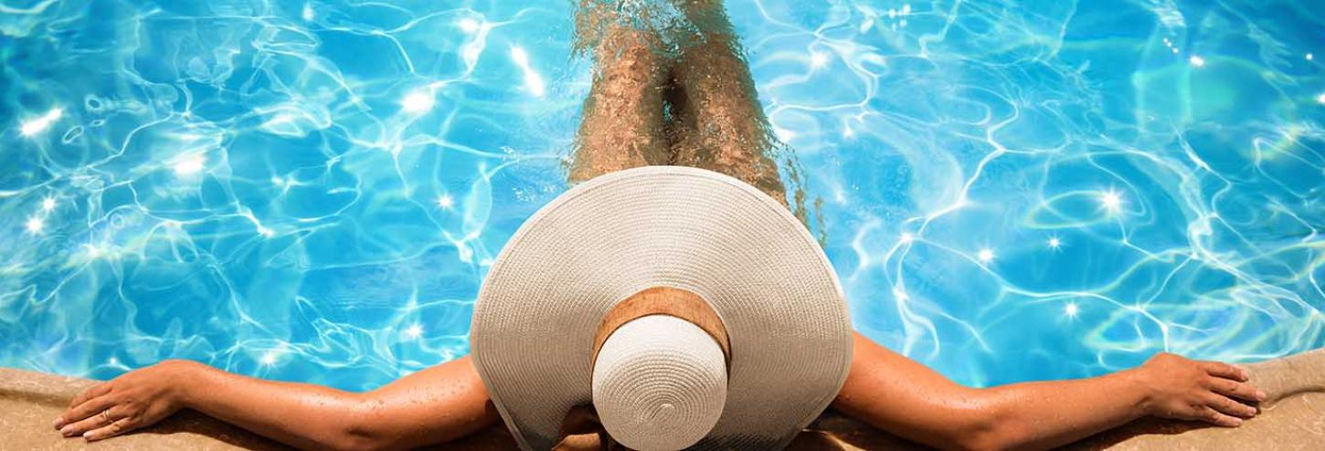 Woman in a sun hat enjoying a private pool