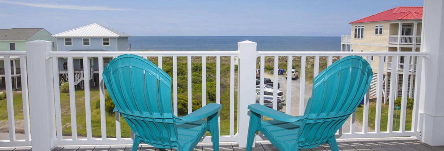 Beach chairs on a front porch looking towards the ocean