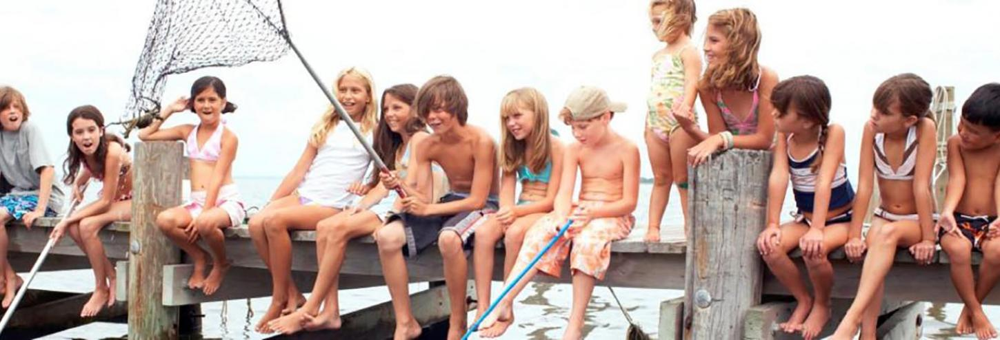 Kids sitting on a dock at a vacation rental home