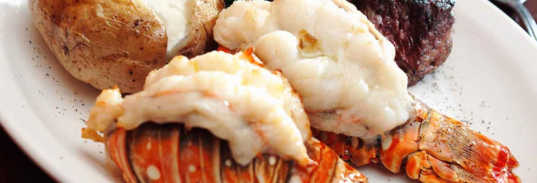 Stuffed lobster tail, steak and potatos