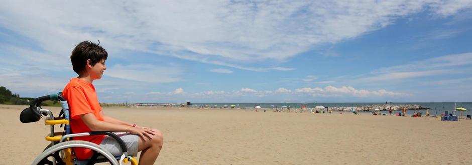 Young boy in a beach wheelchair enjoying Oak Island