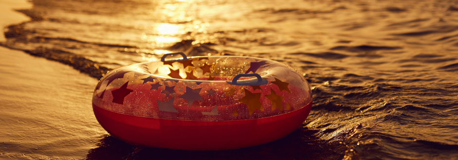 end of summer, inner tube floats in the setting sun in the waves