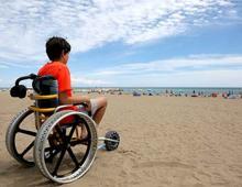 Boy on the beach in a beach wheelchair