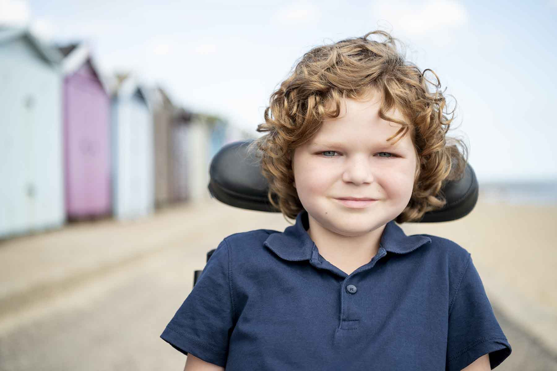 Cute young boy with wavy hair at the beach in his wheelchair