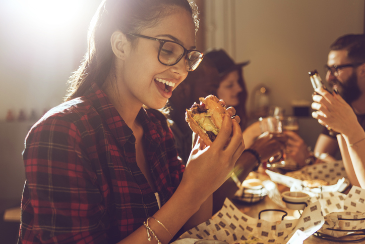 girl in glasses eating a cheeseburger