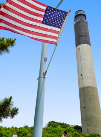 Oak Island Lighthouse on a sunny day with an American flag flying